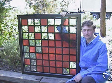 Photo of a man holding a window panel that contains a grid comparing cells that are colored with solar dye against squares with clear glass