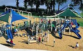 View of a playground showing the gross motor play zone equipped with slides, climbing apparatus, etc.