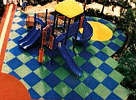 Aerial view of a playground with a green and blue checker-board surface made from rubber mats