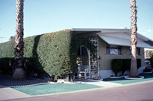 Photo of a one-story house surrounded by foliage for shade.