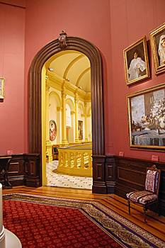 Renwick Gallery, Smithsonian American Art Museum's Octagon Room to Grand Stair Hall prior to renovation with dark coral-colored walls and dark wood trim