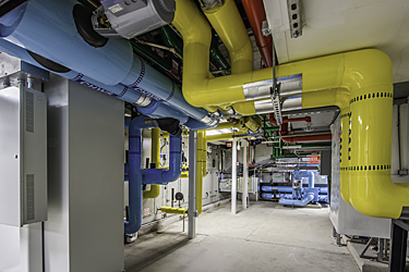 Basement Mechanical Room after restoration with color coded piping jacketing