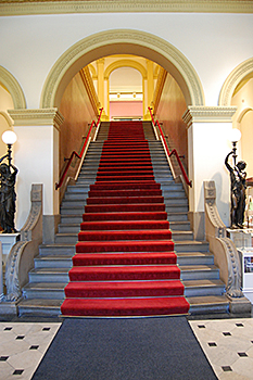 Grand stair in the Renwick Gallery prior to renovation shows gray risers and a dark straight red carpet runner