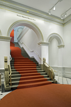 Grand stair in the Renwick Gallery after renovation shows restored rails, risers, and a curving red carpet runner.