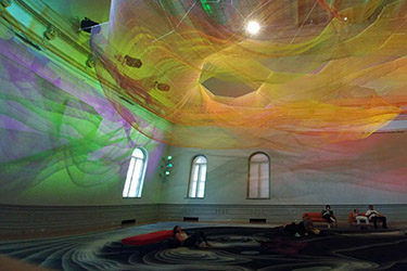 Grand Salon in the Renwick Gallery after renovation showing the installation by Janet Echelman called 1.8, whose swirls of colors and form throughout the space captures the power of the Japanese earthquake from 2011