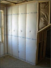 example of a wall being constructed with fiberglass insulation (white paper covering) between the joists