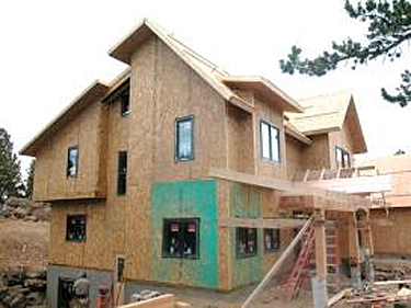 Side view of house construction using SIPs for wall and roof panels in a complicated architectural form
