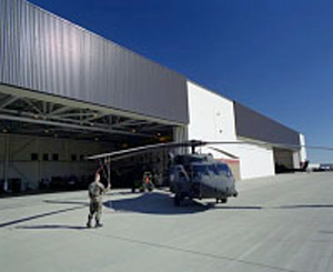Photo of a man in front of a helicopter at Fort Carson U.S. Army Base, south of Colorado Springs, Colorado. A SolarWall solar ventilation air preheating system can be seen attached to the AVUM helicopter maintenance hangar.