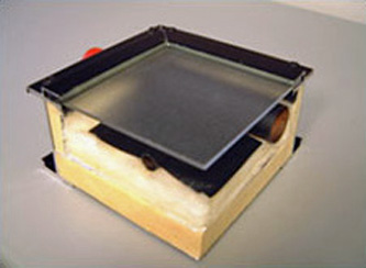 Photo of a mid-temperature flat plate solar collector showing cover glass, insulation, copper absorber plate, and flow passages