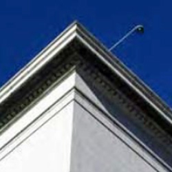 looking up toward a rooftop where a surveillance camera can be seen overhanging the edge