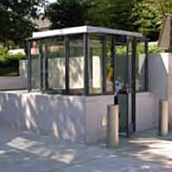 a customed designed guard booth encased with concrete with bollards to the right of it