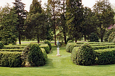 Manicured landscaping featuring a base and statue in a clearing surrounded by hedges on a Virginia Country estate