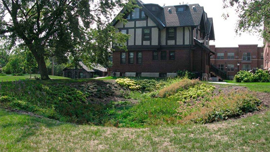 A bio-swale, or depression in the earth, created to redirect rainwater away from the storm sewer system with a large house in the background