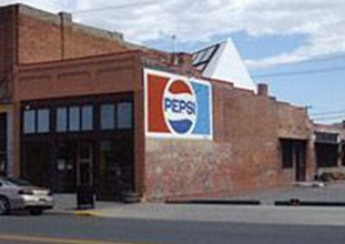 Brick building with Pepsi log painted on the side and solar panel system visible on the back of the roof