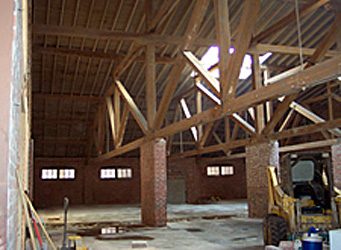 Interiour view of a building the in process of being converted showing the original brick columns, wooden trusses, and skylight