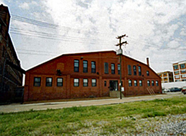 Exterior of a large red brick building with a barn shaped roof