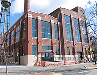 Exterior of a historic red brick building, a former power plant converted to office space, with very large windows that were retained during the converstion