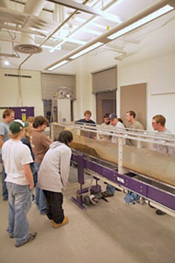 Students gathered around a geology flume lab