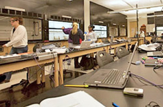 Movable tables in organic chemistry lab with open laptops on counters and students working in the background(Winona State University)