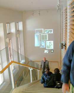 Atrium staircase in Stanford University's Wallenberg Hall with students work projected on the wall