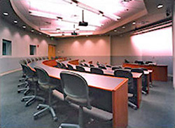 AV equipped classroom with stadium-style setup featuring curved tables and office chairs
