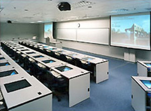 Classroom with fixed desks featuring under-top monitors and presentation screens and board at front of room