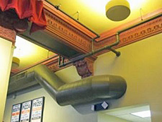 highly ornamented trim work with utility ducts and pipes installed over it which do not meet the Sectretary's standards