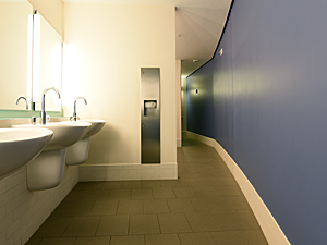 men's bathroom with three sinks and blue curving wall