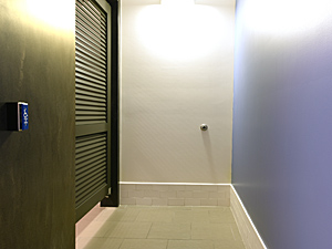 men's bathroom stall with push button door opener and blue wall