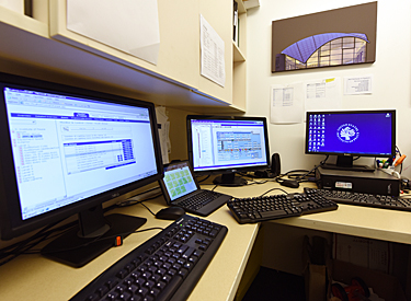 four computer screens engineer uses to monitor building systems