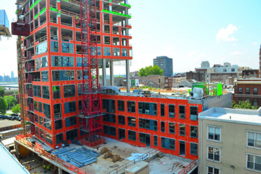 VaproShield WrapShield SA, shown in orange, installed on the Bridge apartment building during construction