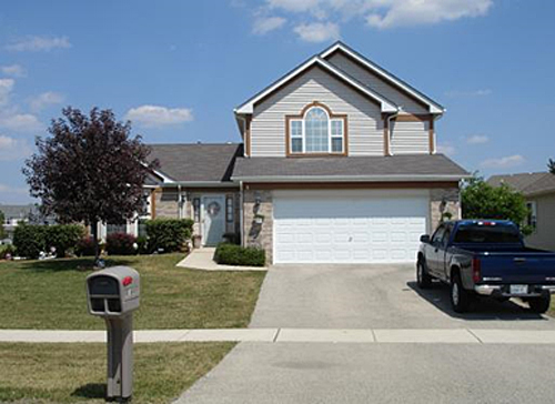 photo of a home with a large single garage door and path from the driveway to the front door