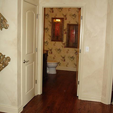 hallway showing the open door of a half-bath on the ground floor of a home