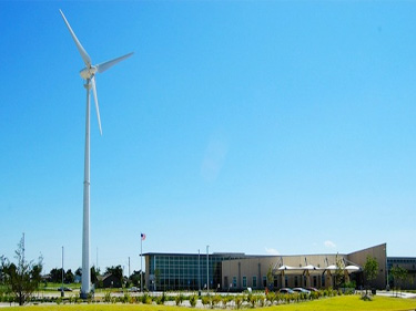 Photo of a distant building with a large wind turbine near to it