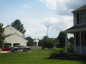 Photo of two residential homes with a wind turbine in the distance between them